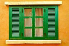 Ventana verde en la pared amarilla Imagenes de archivo