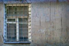 Ventana vieja con una reja oxidada en una pared sucia vieja Imágenes de archivo libres de regalías