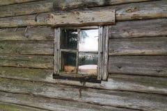 Ventana vieja en la pared del registro de la casa Foto de archivo libre de regalías
