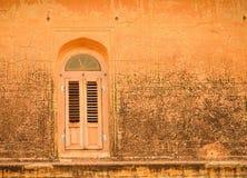 Ventana vieja en una pared anaranjada Imagen de archivo
