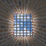 Ventana y barras de las prisiones en pared del ladrillo Imágenes de archivo libres de regalías