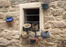 Ventana y macetas de varias formas que cuelgan en una pared hecha de piedras Fotografía de archivo libre de regalías