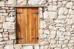 Ventana y obturadores de madera cerrados en la pared de piedra Imagenes de archivo