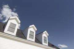 Ventanas abuhardilladas en casa y Windows contra el cielo azul profundo imagen de archivo libre de regalías