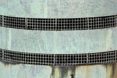 Ventanas asadas a la parrilla estrechas en una pared oxidada del metal imagenes de archivo