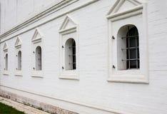 Ventanas barradas en la pared de ladrillo blanca Imagenes de archivo