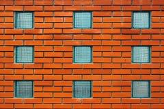 Ventanas cuadradas del bloque de cristal en una pared de ladrillo roja Imagen de archivo libre de regalías