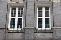 Ventanas de diseño del vintage en la fachada de la casa vieja desigual Imágenes de archivo libres de regalías
