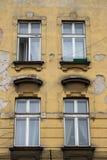 Ventanas de diseño del vintage en la fachada de la casa vieja desigual Fotografía de archivo libre de regalías