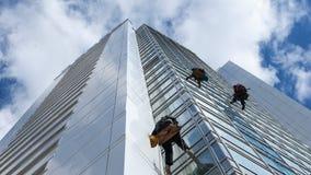 Ventanas de la limpieza del trabajador en altura Foto de archivo