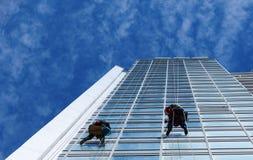 Ventanas de la limpieza del trabajador en altura Fotos de archivo