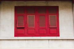 Ventanas de madera rojas viejas en las paredes blancas fotografía de archivo