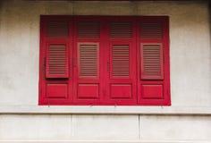 Ventanas de madera rojas viejas en las paredes blancas fotos de archivo