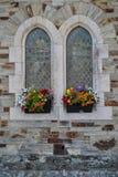 Ventanas del viejo estilo con las cestas de la flor Imagen de archivo libre de regalías