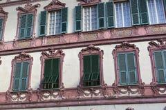 Ventanas italianas viejas, abiertas, en una pared pintada descolorada con los obturadores Foto de archivo