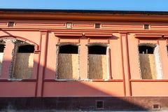 Ventanas quebradas y dañadas con el agujero en la fachada de la casa o del edificio que espera para ser substituido cerrado y ase fotos de archivo libres de regalías