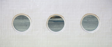3 ventanas redondas en una pared tejada blanca Fotos de archivo