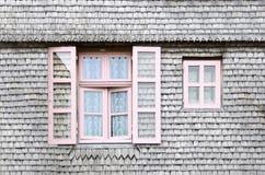 Ventanas rosadas hermosas en fachada de una casa de madera Imagen de archivo libre de regalías