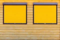 ventanas simétricas con los obturadores amarillos cerrados imágenes de archivo libres de regalías