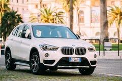 Ventanas viejas hermosas en Roma (Italia) El coche blanco de BMW X1 del color de la segunda generación F48 parqueó en la calle fotos de archivo libres de regalías