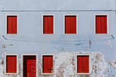 Ventanas y puerta de madera rojas en la pared azul clara vieja, en el islan foto de archivo