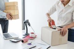Ventas en l?nea del env?o, peque?a empresa o servicio de entrega del due?o del empresario de la PME y caja de embalaje de trabajo imagen de archivo libre de regalías