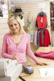 Ventas femeninas auxiliares en almacén de ropa Fotografía de archivo libre de regalías