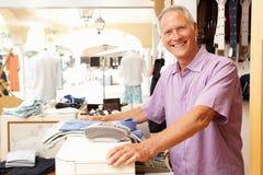Ventas masculinas auxiliares en la comprobación del almacén de ropa Fotografía de archivo libre de regalías