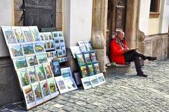 Ventas masculinas del artista sus pinturas en las calles Muchos artistas de la calle dibujan y venden pinturas en la calle Szente Foto de archivo