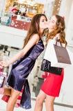 Vente, achats et concept heureux de personnes - deux belles femmes avec des paniers fille embrassant l'amie Photographie stock