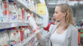 Vente, achats, personnes de consommationisme femme avec le panier à provisions choisissant des produits dans le supermarché Fille banque de vidéos
