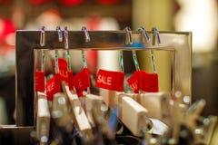 Vente d'étiquette rouge avec le pantalon sur un cintre dans le magasin Photographie stock libre de droits