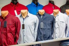 Vente d'habillement du ` s des hommes Chemises du ` s d'hommes sur les mannequins dans le magasin image libre de droits