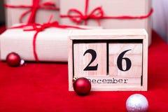 Vente de lendemain de Noël Calendrier avec la date sur le fond rouge Concept de Noël 26 décembre Boule et cadeaux de Noël Images libres de droits