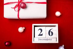 Vente de lendemain de Noël Calendrier avec la date sur le fond rouge Concept de Noël 26 décembre Boule et cadeaux de Noël Vue sup Images stock