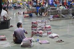 Vente des journaux du matin sur une station de Mumbai Photographie stock libre de droits