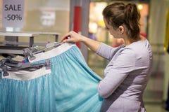 Vente des vêtements dans la boutique de mode la fille choisit des vêtements dans le magasin Black Friday dans les centres commerc Photos libres de droits