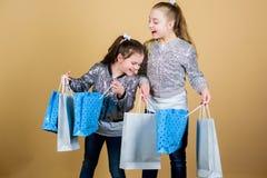 Vente et remise Jour d'achats Les enfants tiennent des paquets de groupe mode de gosses Attendez plus Payez moins Soeurs de fille image stock