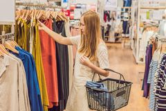 Vente, mode, consommationisme et concept de personnes - jeune femme heureuse avec des paniers choisissant des vêtements dans le m photos stock