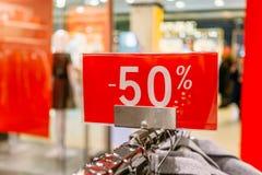 Vente 50 pour cent outre des lettres sur la bannière rouge à l'intérieur du magasin populaire de mode photo stock
