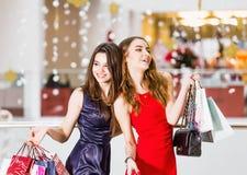 Vente, tourisme, achats et concept heureux de personnes - deux belles femmes avec des paniers au centre commercial Image stock