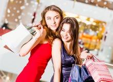 Vente, tourisme, achats et concept heureux de personnes - deux belles femmes avec des paniers au centre commercial Image libre de droits