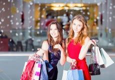 Vente, tourisme, achats et concept heureux de personnes - deux belles femmes avec des paniers au centre commercial Photographie stock