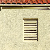 Vented Window Under a Red Tile Roof Royalty Free Stock Image