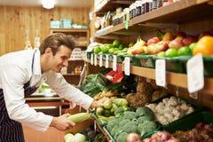 Ventes masculines auxiliaires au compteur végétal de la boutique de ferme photo stock