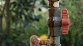 Ventil för rör för rött vatten för tappning i trädgård arkivfoton