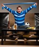 Ventilador de fútbol en el sofá Imagen de archivo libre de regalías
