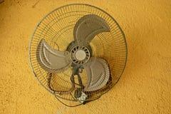 ventilador do vintage no muro de cimento amarelo imagem de stock royalty free