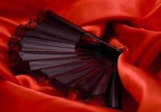 Ventilador en el satén rojo Imagen de archivo