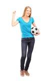 Ventilador fêmea feliz que guardara um futebol e gesticular Imagens de Stock Royalty Free